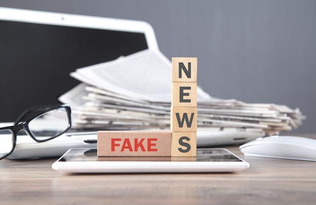 新聞と眼鏡で木製の立方体に偽のニュースをテキストで送信します。