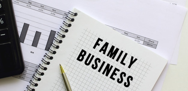 Text family business on the page of a notepad lying on financial charts on the office desk.
