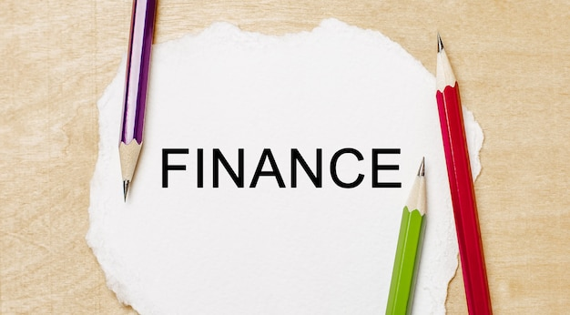 Text finance on a white notepad with pencils on a wooden background. business concept