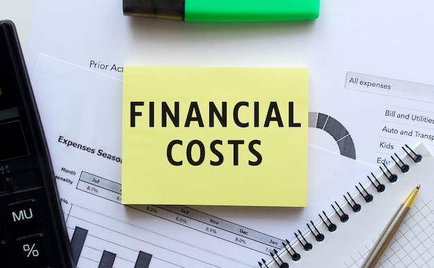 Text financial costs on the page of a notepad lying on financial charts on the office desk. near the calculator.