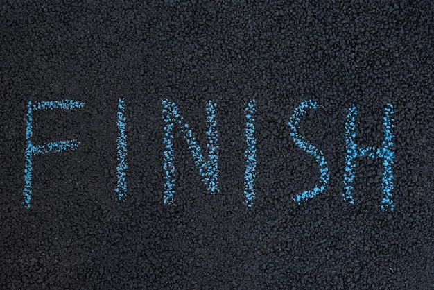 Text finish underfoot. black asphalt with chalk inscription. the end concept