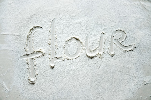 Text on the flour scattered on the table. texture flour. top view flat lay..