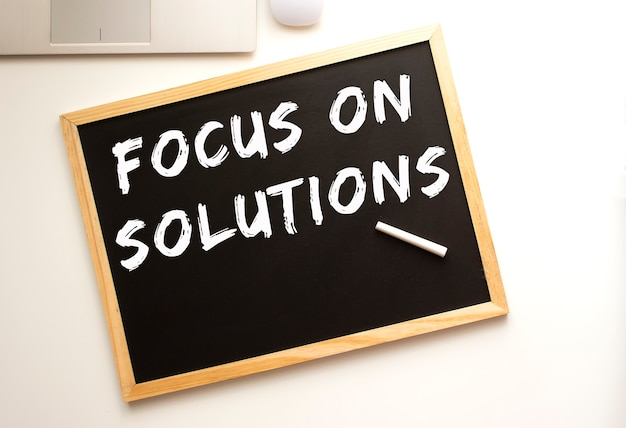 Text focus on solutions written in chalk on a slate board. office desk. business concept.