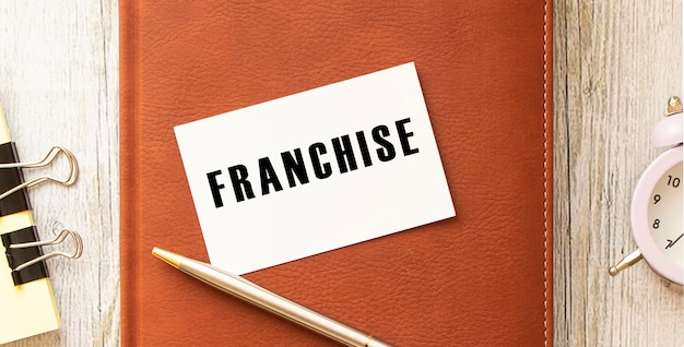 Text franchise on white card lying on notepad on office desk