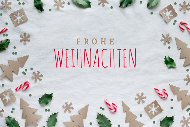 Text frohe weihnachten means merry christmas in german. eco friendly decor from craft paper, red white candy canes and natural green holly leaves. xmas tree silhouettes, snowflakes and circles.
