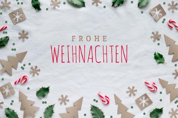 Текст frohe weihnachten на немецком языке означает «с рождеством». экологичный декор из крафт-бумаги, красно-белых леденцов и натуральных зеленых листьев падуба. рождественские силуэты деревьев, снежинки и круги.