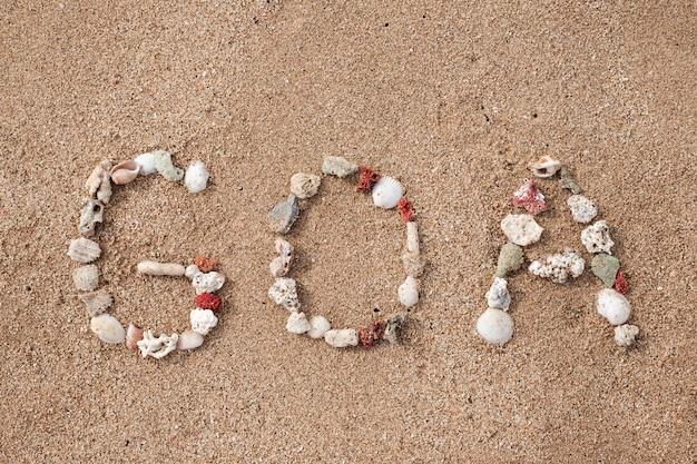 Text goa made from shells on seashore on sandy beach