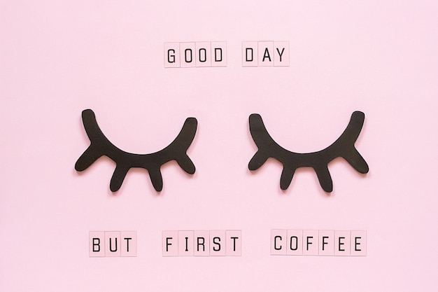 Text good day, but first coffee and decorative wooden black eyelashes, closed eyes, on pastel pink paper