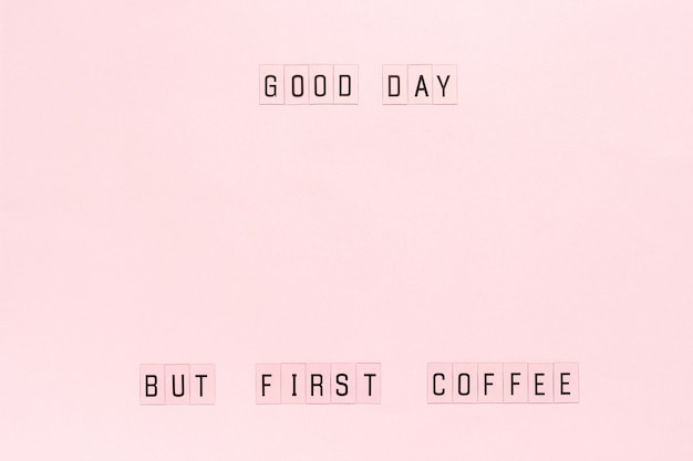 Text good day, but first coffee on pastel pink paper background.