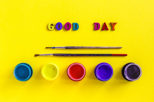 Text good day, jars with gouache and paintbrushes on yellow background
