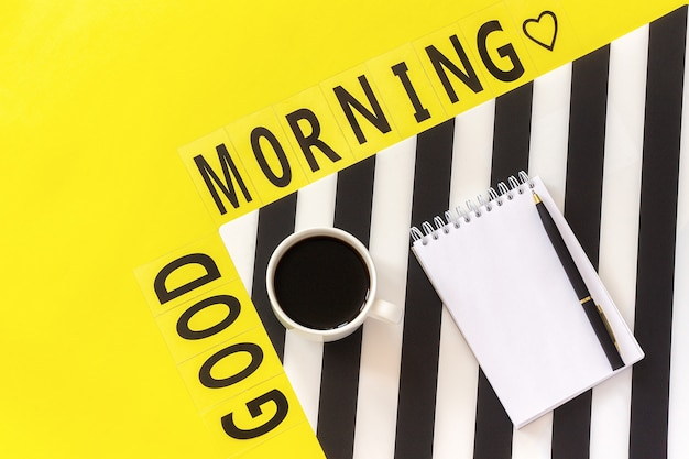 Text good morning, coffee, notebook for text on stylish black and white napkin on yellow background. concept good morning