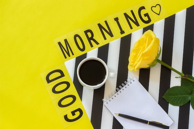 Text good morning, cup of coffee, donut, rose, notepad concept stylish workplace