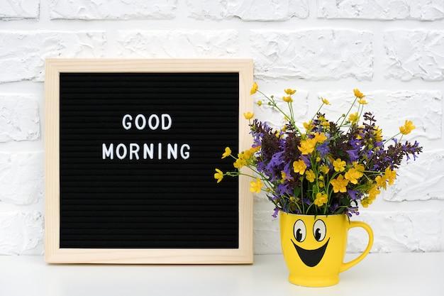 검은 편지 보드와 노란색 컵에 착 색된 한 꽃의 꽃다발에 텍스트 좋은 아침