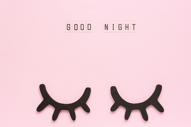 Text good night and decorative wooden black eyelashes, closed eyes on pink paper background.