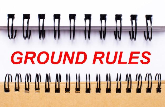 Напишите основные правила на белой бумаге между белыми и коричневыми спиральными блокнотами.