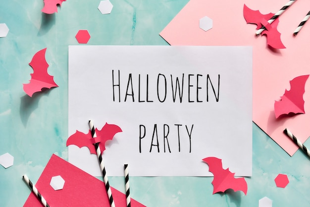 Text halloween party. flat lay, trendy halloween decorations - hexagon confetti, paper drinking straws, flying bats and spiders.