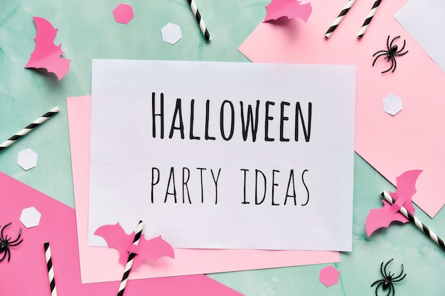 Text halloween party ideas on layered paper with halloween decorations