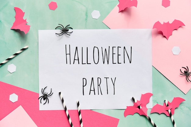 Text halloween party on layered paper background in mint green and pastel pink. flat lay, halloween party decor.