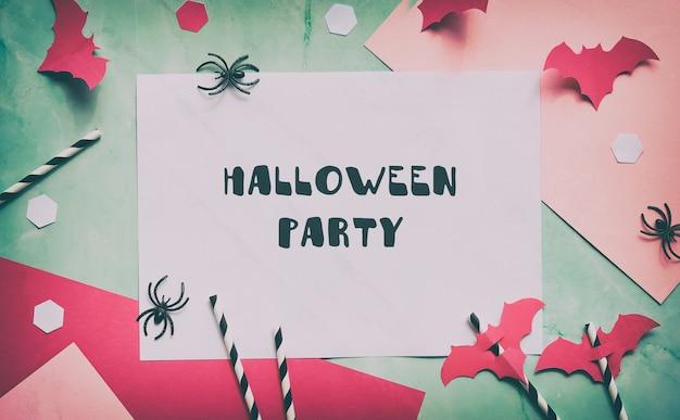 Текст «хэллоуин» на многослойной бумаге мятно-зеленого и пастельно-розового цветов.