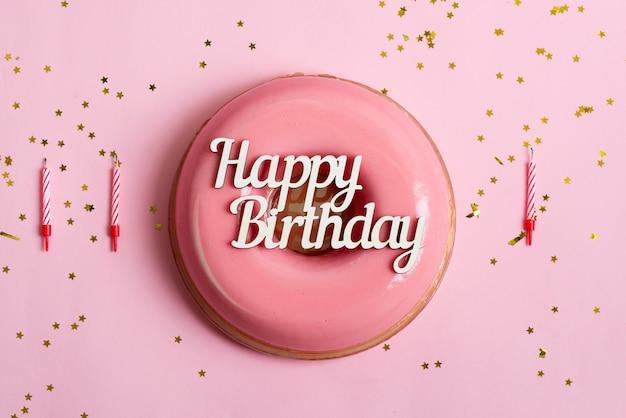 キャンドルと装飾が施されたピンクの背景に、焼きたての自家製フルーツの艶をかけられたデザートの上のテキストハッピーバースデー。