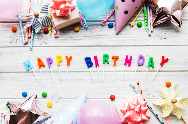 Text happy birthday by candle  letters with birthday accessories, candles and confetti on white wooden