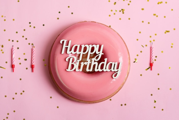Text happy birthday above freshly cooked homemade fruit glazed dessert on a pink background with candles and decoration.