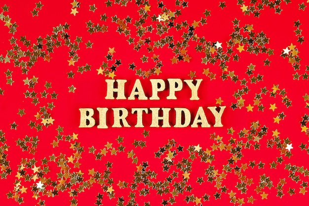 Text happy birthday laid out of gold letters on beautiful . golden stars confetti.