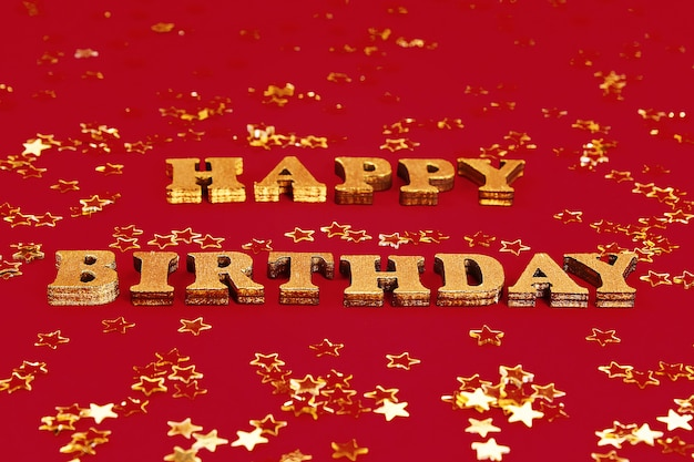 Text happy birthday laid out of gold letters. golden stars confetti.