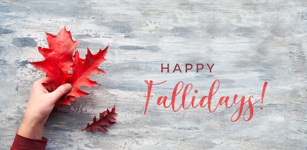 テキストハッピー秋。フラット横たわっていた、トップビュー、テクスチャの灰色の木に赤いカシの葉と小枝を持っている手
