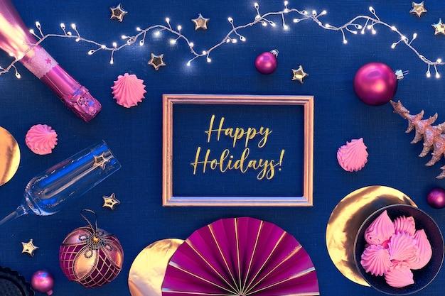ゴールデンフレームのテキストハッピーホリデー。白いお皿、シャンパン、金色の道具、濃い赤の金色の装飾が施されたクリスマステーブルのセットアップ。