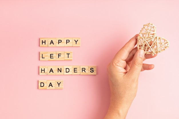 Text happy left handers day written with wooden letters and heart over pink background