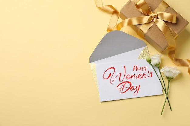 베이지 색 배경에 텍스트 행복한 여성의 날, 장미, 봉투 및 선물 상자