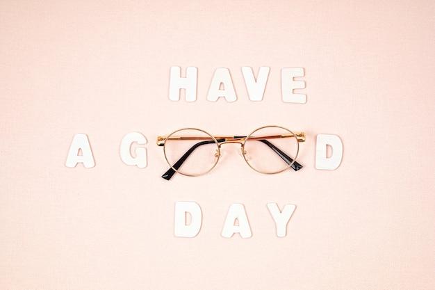 Желаем хорошего дня в очках на светло-розовой стене. мотивационная цитата. плоская планировка, вид сверху