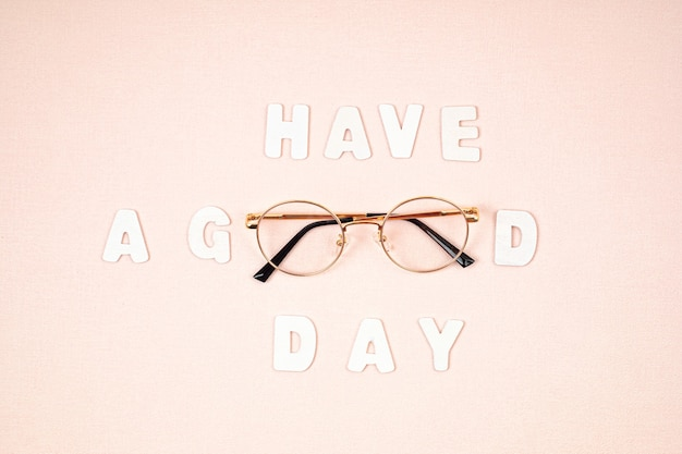 Text have a good day with glasses over the light pink wall. motivation quote. flat lay, top view