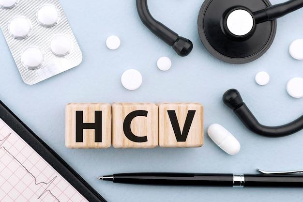 木製のブロック、聴診器、錠剤、カプセル、心電図にhcvをテキストで送信します。医療の概念。フラットレイ。