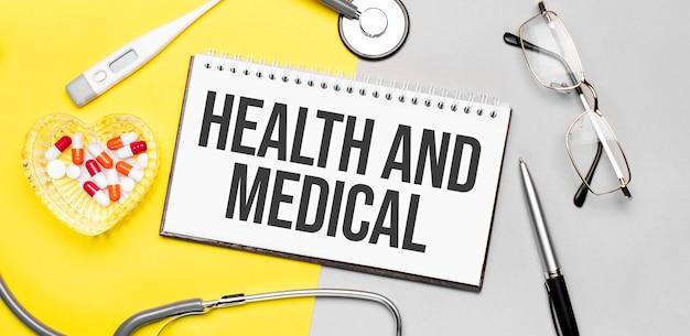 聴診器、眼鏡、ペン、温度計、赤い錠剤、黄色の表面にペンを置いたノートに健康と医療のテキストを表示