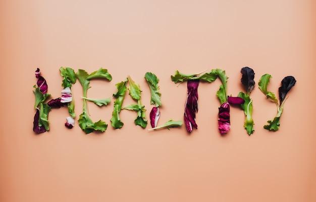 Текст здоровый, используя смесь зеленых и фиолетовых листьев салата на бежевом фоне. фото высокого качества