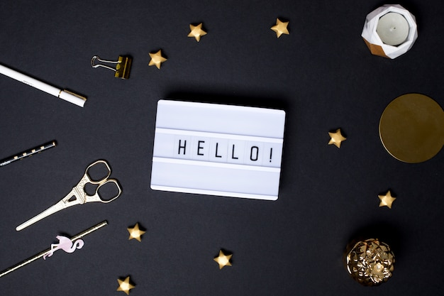 Text hello on a black table with a gold stars