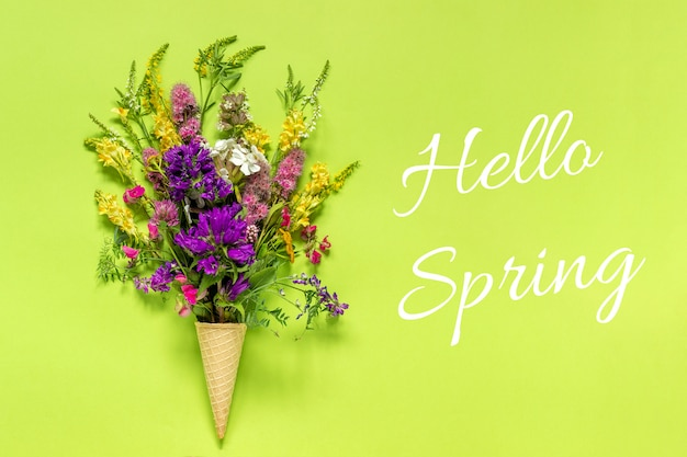 Text hello spring bouquet field colored flowers in waffle ice cream cone on green background