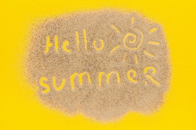 Text hello summer and sun sign drawn on sand on yellow paper background concept vacation