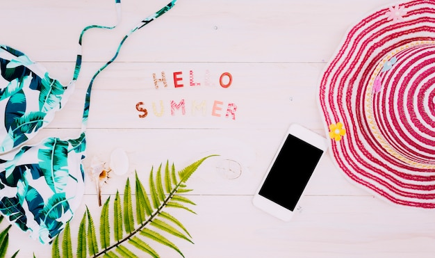 Text hello summer with beach things on light surface