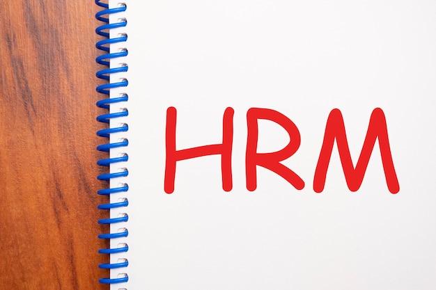 Текст hrm, написанный в блокноте, офисный деревянный стол сверху, концепция