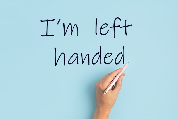 Text i am left handed and left hand with pen over blue background. international left handers day concept