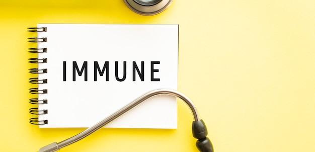Текст immune на блокноте со стетоскопом