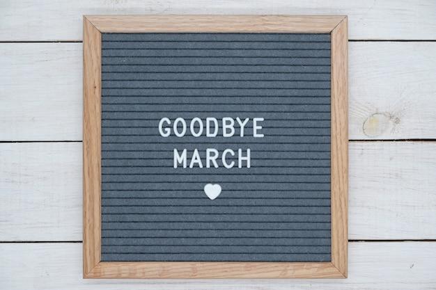 英語のさようならマーチのテキストと木製フレームの灰色のフェルトボード上のハートのサイン。