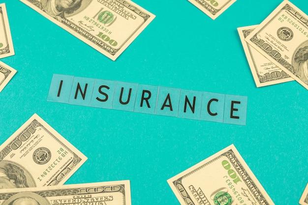 オフィスのデスクトップ上のドル紙幣の周りのテキスト保険、明るいビジネスの背景写真