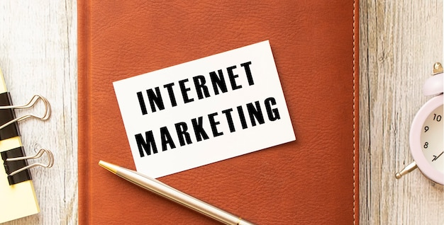 オフィスの机のメモ帳に横たわっている白いカードにテキストインターネットマーケティング