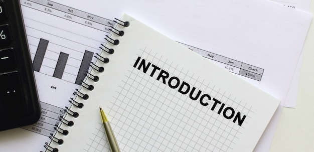 Text introduction on the page of a notepad lying on financial charts on the office desk. near the calculator. business concept.