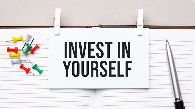 사무용 도구를 사용하여 일기의 스티커에 invest in yourself 텍스트