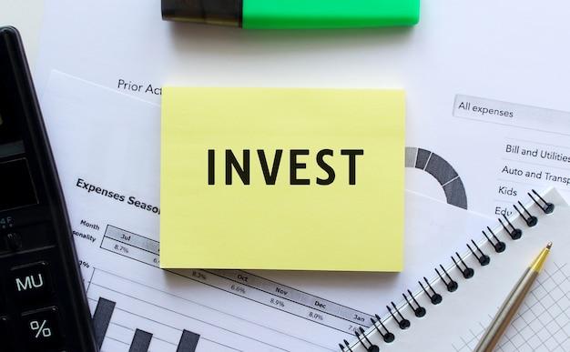 사무실 책상의 금융 차트에 누워있는 메모장 페이지에 invest 텍스트